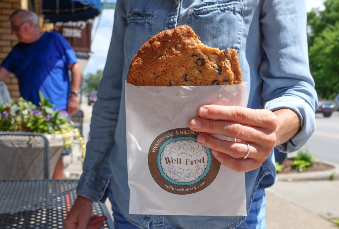 A woman holding a cookie from Well-Bred Bakery in Weaverville, NC