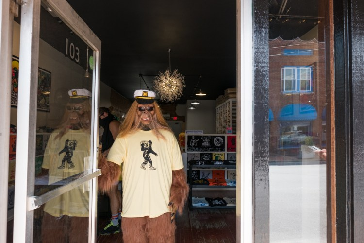 a photo of a bigfoot standing in a doorway in downtown Black Mountain wearing a t-shirt and sailors cap and sunglasses.
