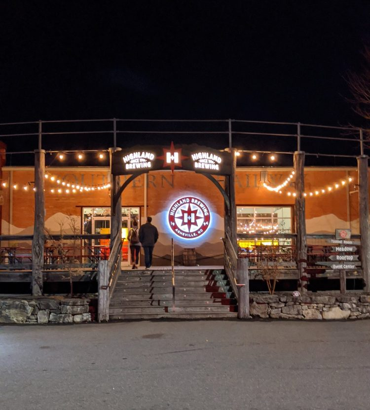 Two people walking into the front doors at Highland Brewing Company at night. There is a sign with the Highland logo and it is lit up.