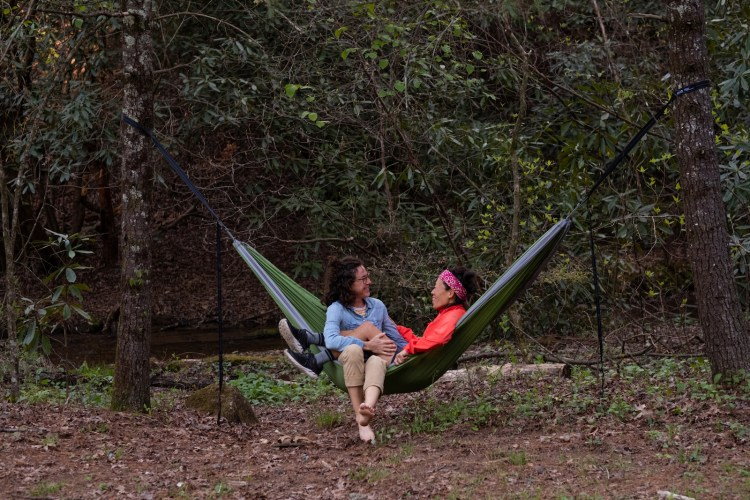 Two women hammocking in a green ENO hammock in Bent Creek. The hammock is strung between two trees. A small creek flows in the background. One of the women is barefoot.