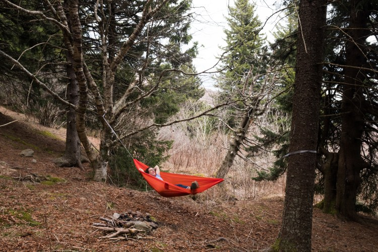 Caroline Whatley hammocking near Asheville, NC in a bright orange ENO hammock near Black Balsam Knob. She is laying down and looking up with her arms behind her head.