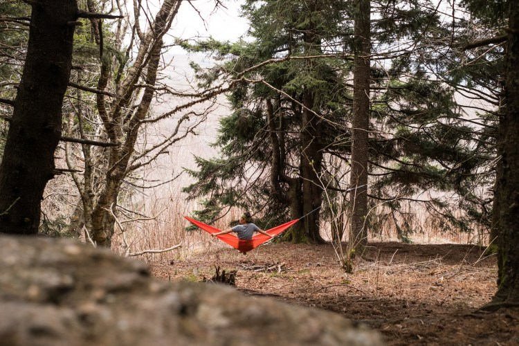 Erin McGrady sits in a bright orange ENO hammock and looks out towards the mountains. A rock is blurred out in the foreground.