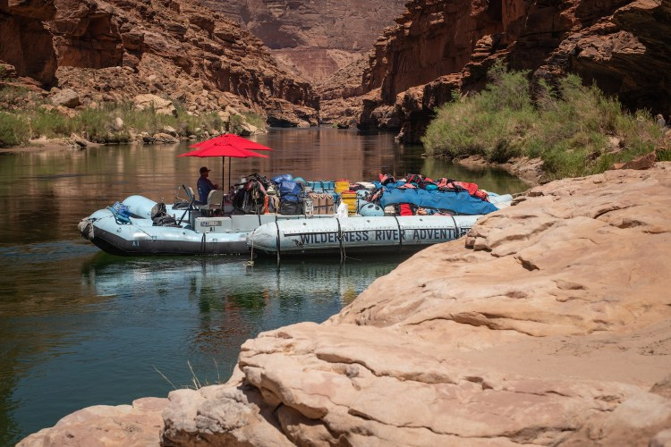 Wilderness River Adventures' blue raft is anchored in a calm spot along the Colorado River in the Grand Canyon. Two red umbrellas are up and the boatman is under one of them for shade.