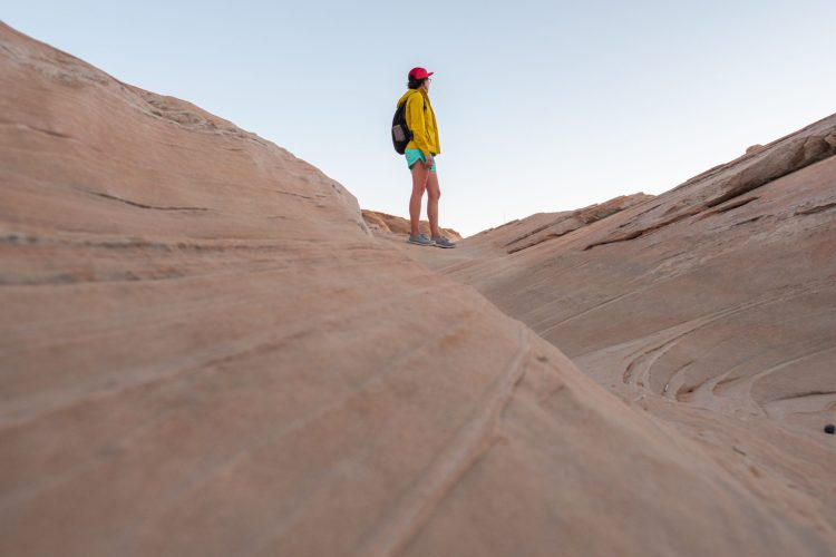 Caroline Whatley is in a red hat, yellow jacket, and mint green shorts. She is standing on reddish slickrock and looking out into the distance.