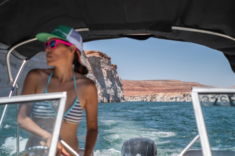 Erin McGrady has a green trucker hat and pink sunglasses on. She is steering a powerboat on Lake Powell. The red rock in the area is in the background as is the top portion of the boat's motor.