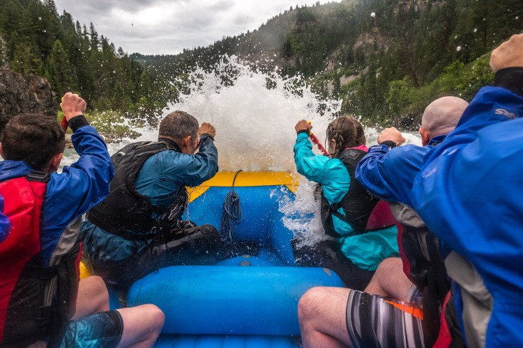 A raft of people sitting on a blue raft are holding paddles which are plunged into the water. They face a big oncoming spray of whitewater at the bow of the raft.