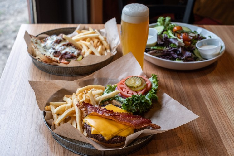an open-faced cheeseburger with bacon on top and a side of fries as well as lettuce, tomato, and pickle is in the foreground. A thin-sliced roast beef sandwich with mozzarella cheese and a salad and a tall glass of beer are in the background at the Red Fox Saloon.
