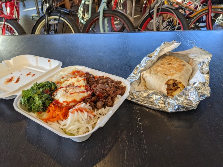 Beef bibimbap is sitting in a container on top of a black table at New Belgium Brewing in Asheville, NC. A burrito is also on the table partially wrapped in foil. Bikes are in the background.