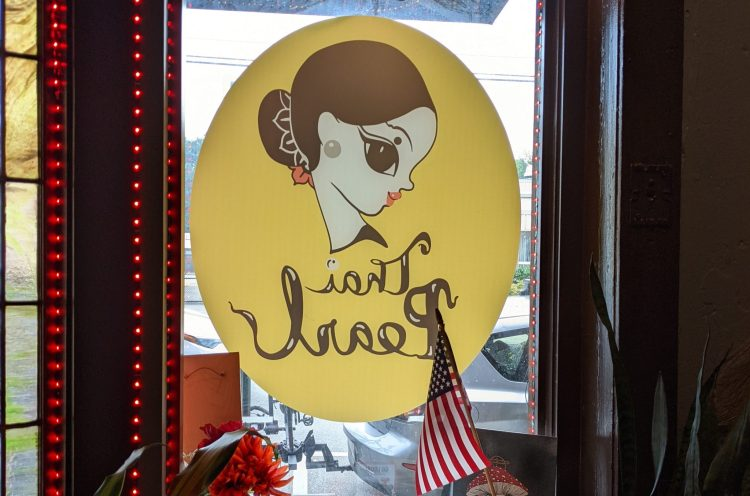a photo of Thai Pearl's logo painted on their window in West Asheville. The logo, which is yellow with black and white words in cursive, is backwards, as the photograph was taken inside the restaurant. A cartoonish drawing of a woman is above the words Thai Pearl. An American flag is in the foreground and red lights frame the window.
