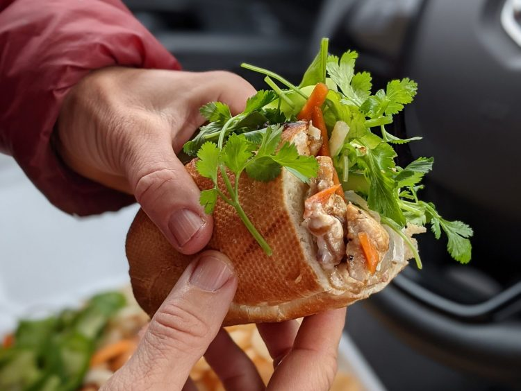 A photo of half of a banh mi sandwich from Wild Ginger is held in Caroline Whatley's hand. A steering wheel and a to-go container is blurred out in the background.