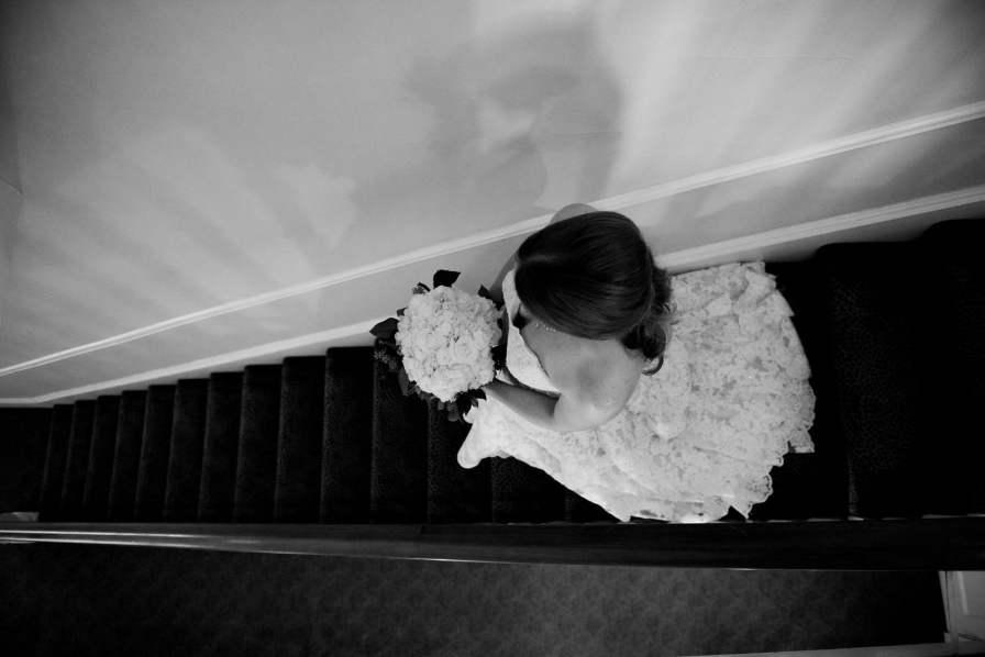 Bride walking down staircase in Flint Hill house