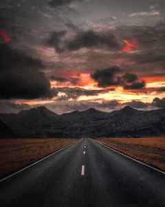 A road stretching into the distance with mountains and a sky filled with dark clouds and a red and orange sky.