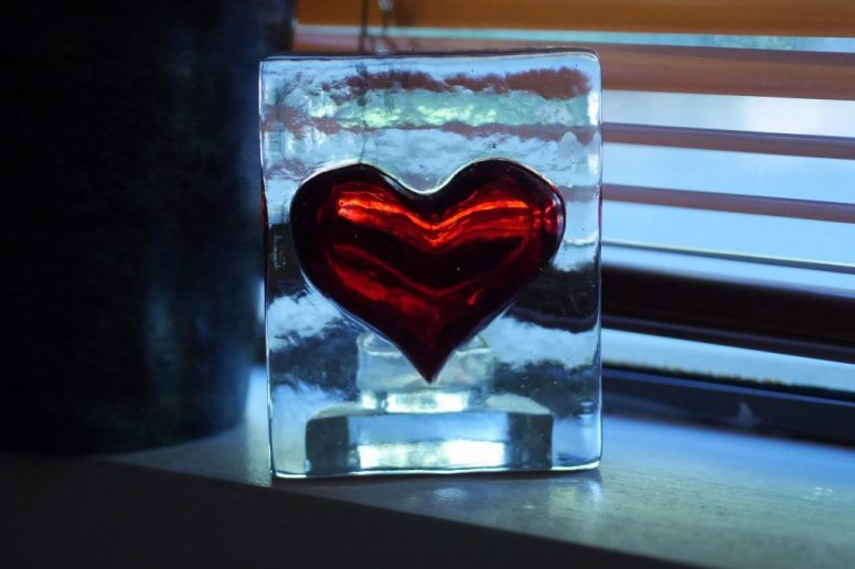 A red heart inside of a rectangular glass container.