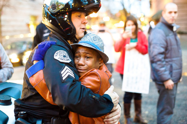 Boy and police officer hugging in Portland Oregon