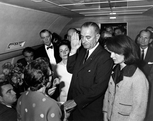 ST-1A-1-63 22 November 1963 Judge Sarah T. Hughes administers the Presidential Oath of Office to Lyndon Baines Johnson aboard Air Force One, at Love Field, Dallas Texas. Mrs. Johnson, Mrs. Kennedy, Jack Valenti, Cong. Albert Thomas, Cong. Jack Brooks, Associate Press Secretary Malcolm Kilduff (holding microphone) and others witness. Photograph by Cecil Stoughton, White House.