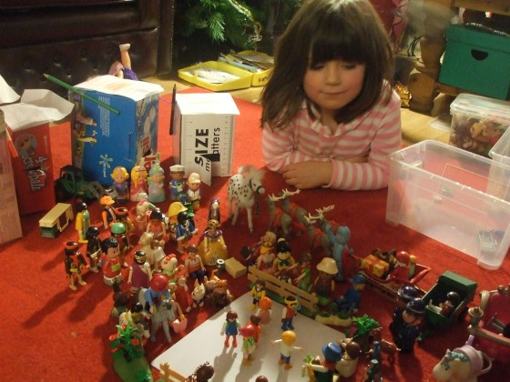 Photo of young Laura playing with Playmobil figures at Christmas