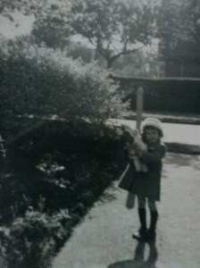 The author aged about 5, with a teddy, in her front garden