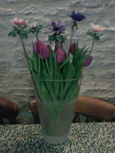 Tulips and anemones stuffed tightly into a glass vase