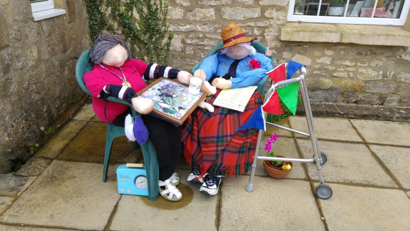 Photo of two scarecrows with a zimmer frame, radio and cups of tea