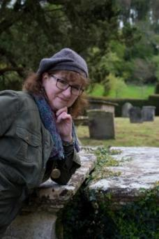 photo of Debbie leaning on a tomb in Hawkesbury churchyard