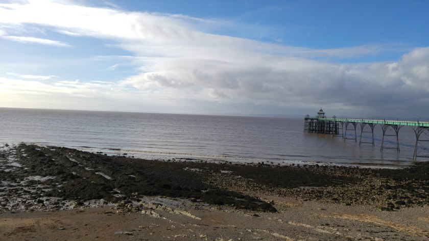 long shot of pier viewed across beach