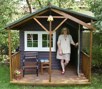 Debbie Young on the porch of her writing hut