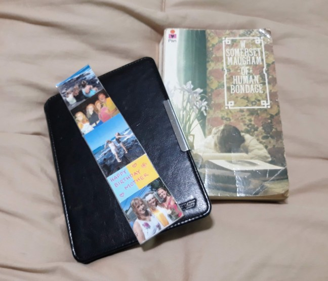 photo of kindle e-reader, bookmark and paperback book