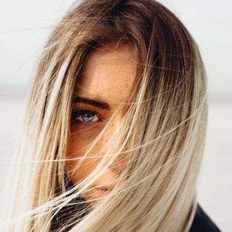 blonde woman blue eyes hair over face