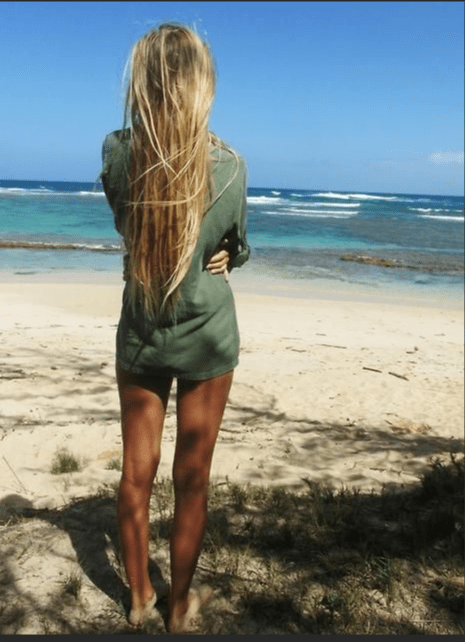 blonde woman from the back looking at ocean and beach
