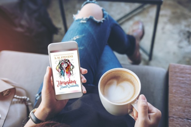 woman holding iphone with horseshoes and hand grenades novel on screen and cup of coffee