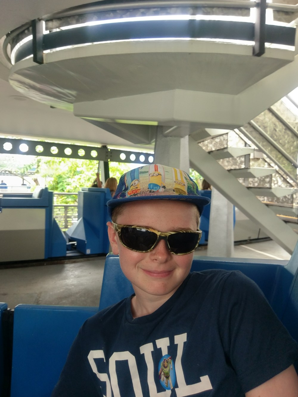 A boy in sunglasses, smiling as he sits on a Disney ride