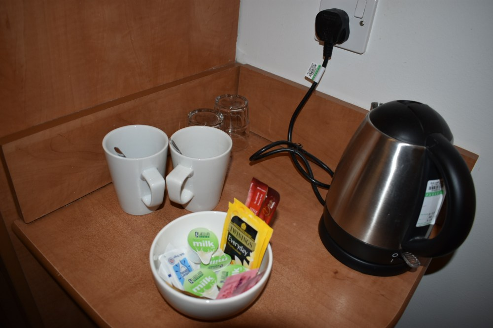 A kettle, cups, glasses and a bowl of tea, coffee, milk and sugar.
