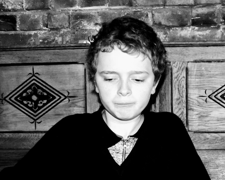 A black and white photo of a boy looking down.