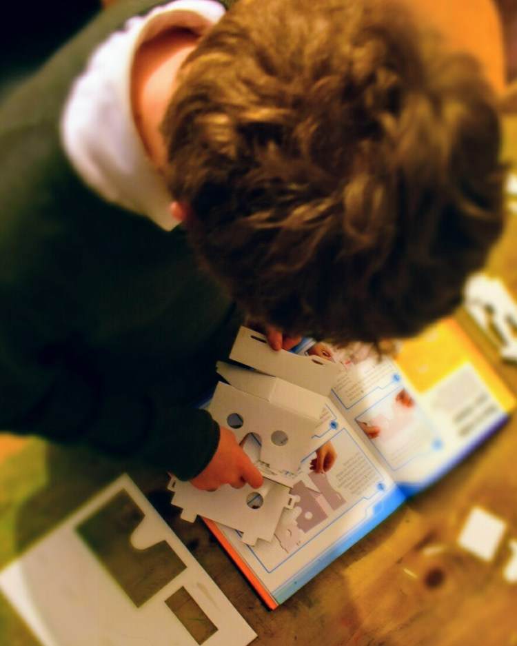 A picture from above of a boy following instructions to make a virtual reality viewer