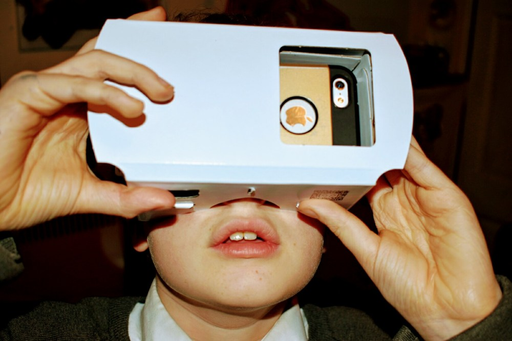 A child holding a Virtual Reality viewer to their eyes. The child looks amazed.