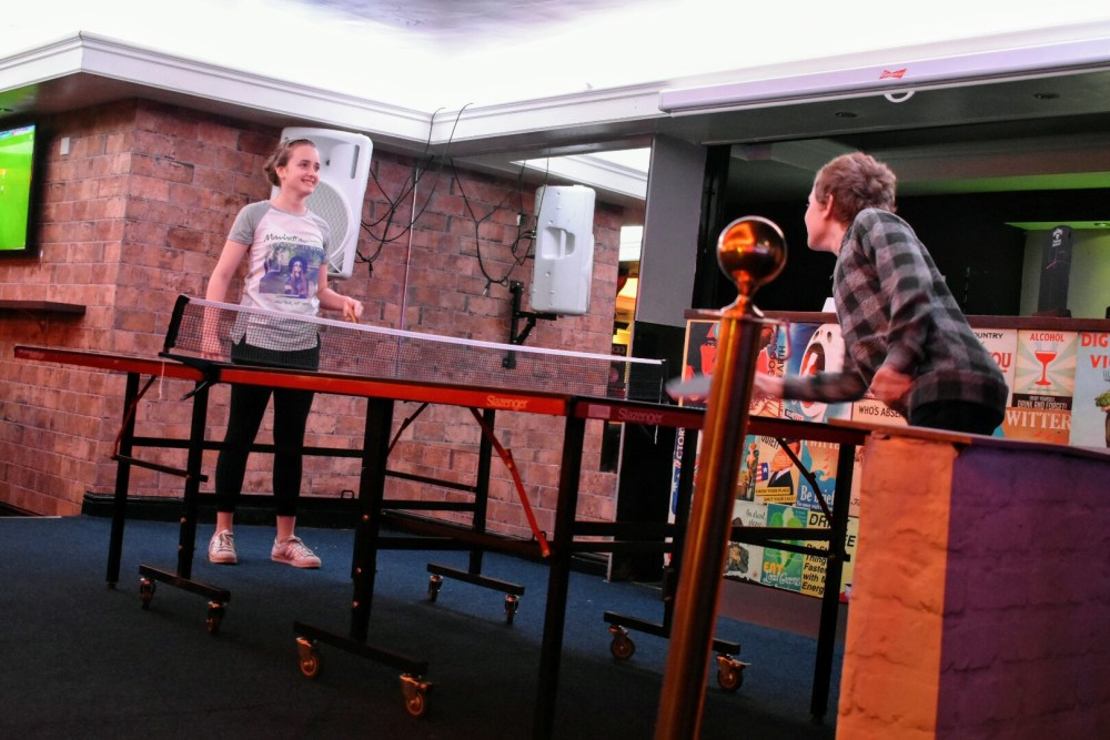 A boy and a girl having fun, playing table tennis