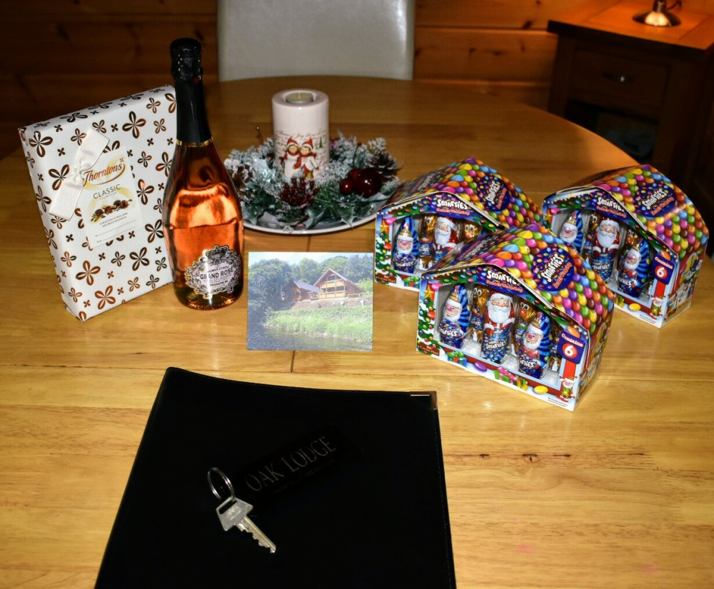 A table with a welcome Christmas card, three smarties Christmas treats, a box of thorntons chocolates and a bottle of sparkling rose wine