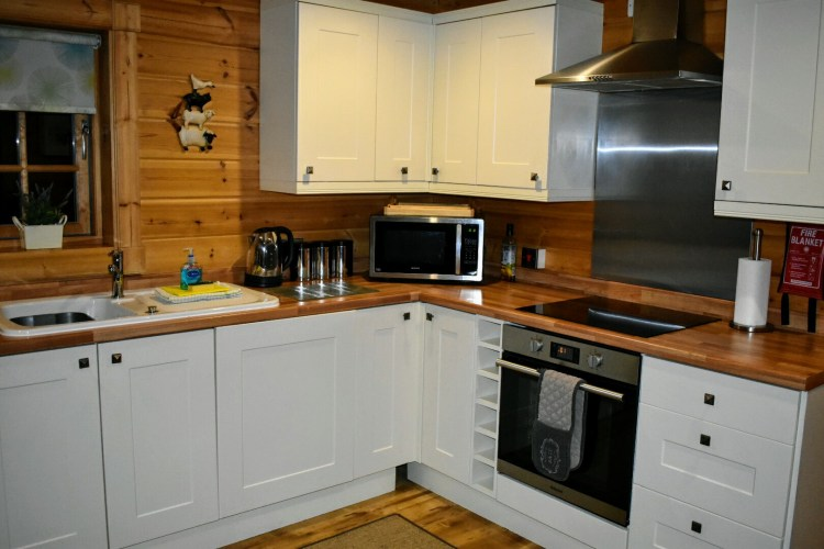 A kitchen with oven, microwave, kettle and sink