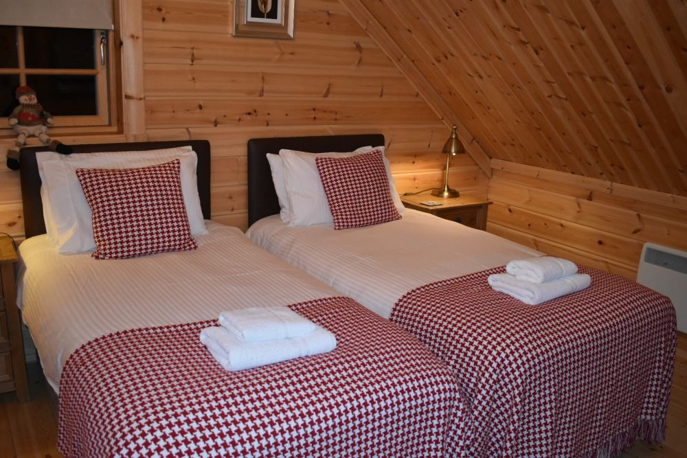 Two single beds with white bedding and red and white checkered bed spreads