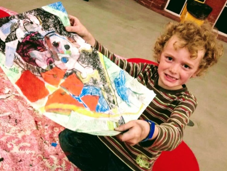 A child holding up a picture he has made. He is smiling happily.