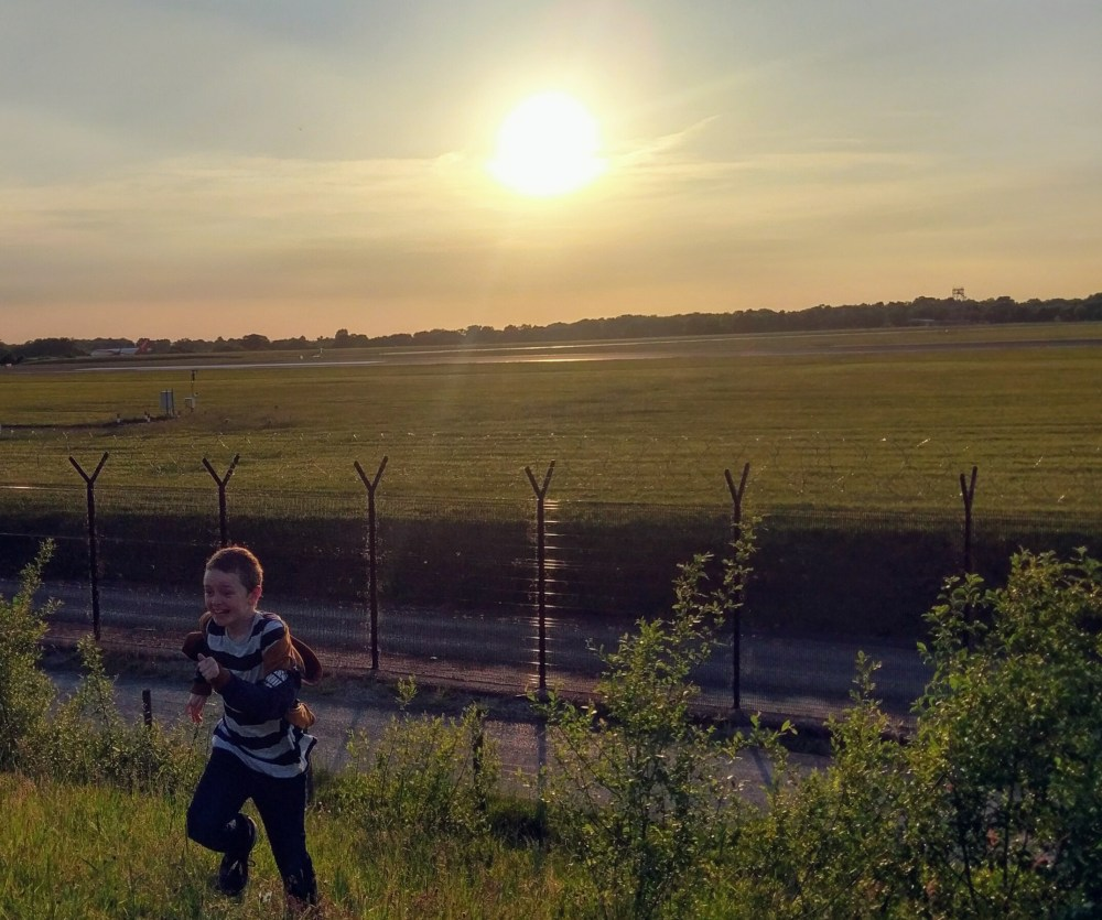 A happy child running up a hill with the sun setting behind.