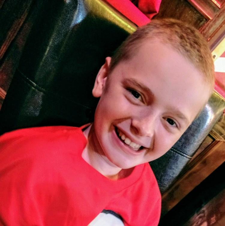 A happy boy in a red Tshirt, smiling