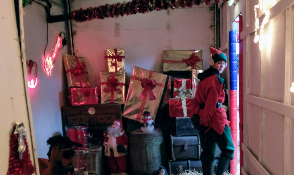 A lady dressed as an elf in a small room with a huge pile of presents behind her.