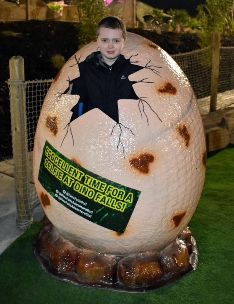 A boy posing in a dinosaur egg