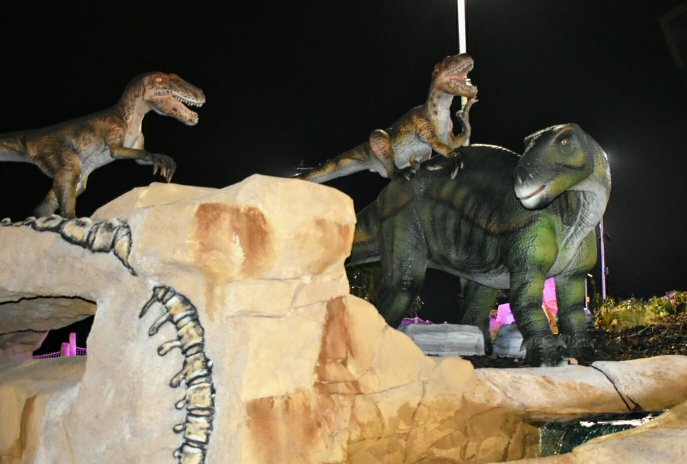 Three dinosaurs on a rock