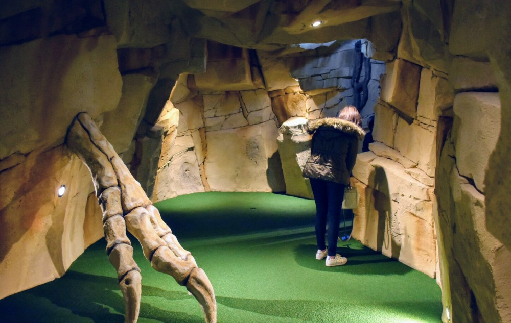 A girl in a cave playing golf