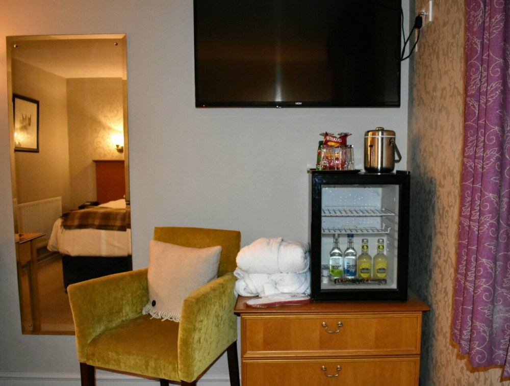 An armchair and fridge. The bed can be seen in the mirror