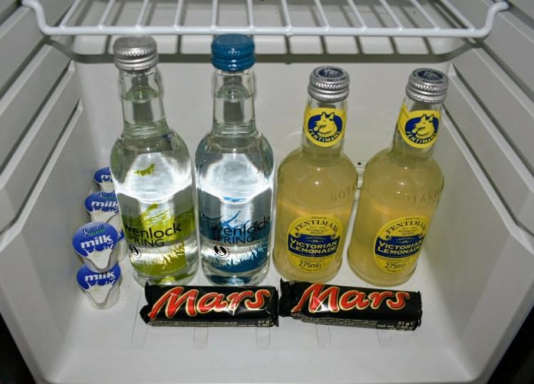 An open fridge containing water, lemonade, milk and mars bars