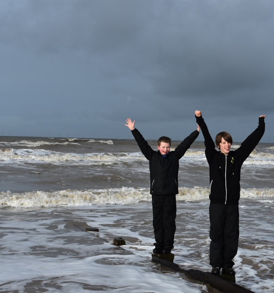 Two boys on the beach waving their hands in the air