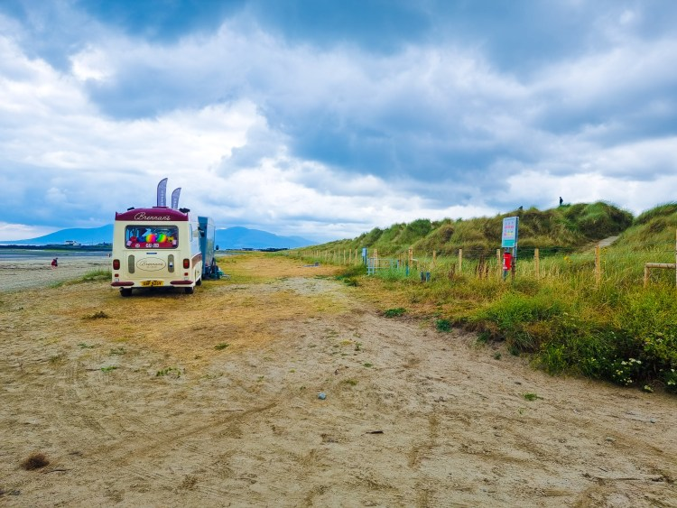 Tyrella beach in Northern Ireland with vast sand, sand dunes and sea. Backed by the Morne mountains wit ice cream van.
